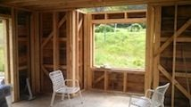 Picture of house interior under construction with board sheathing and let-in bracing